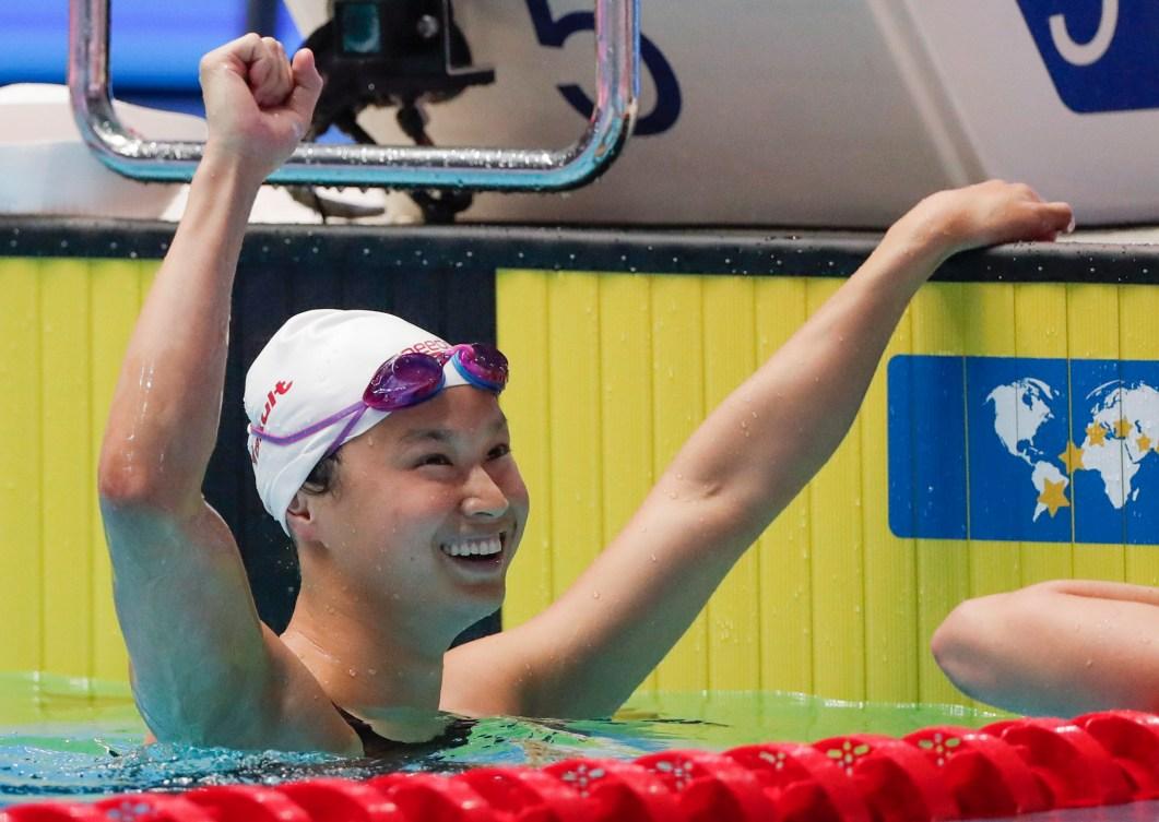 Maggie MacNeil raises a fist in celebration after winning the women's 100m butterfly title.