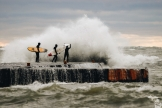 Three surfers in thick wetsuits bracing for a wave
