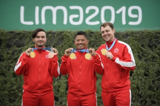 Three athletes pose with their medals.