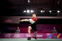 badminton player reaches for the birdie