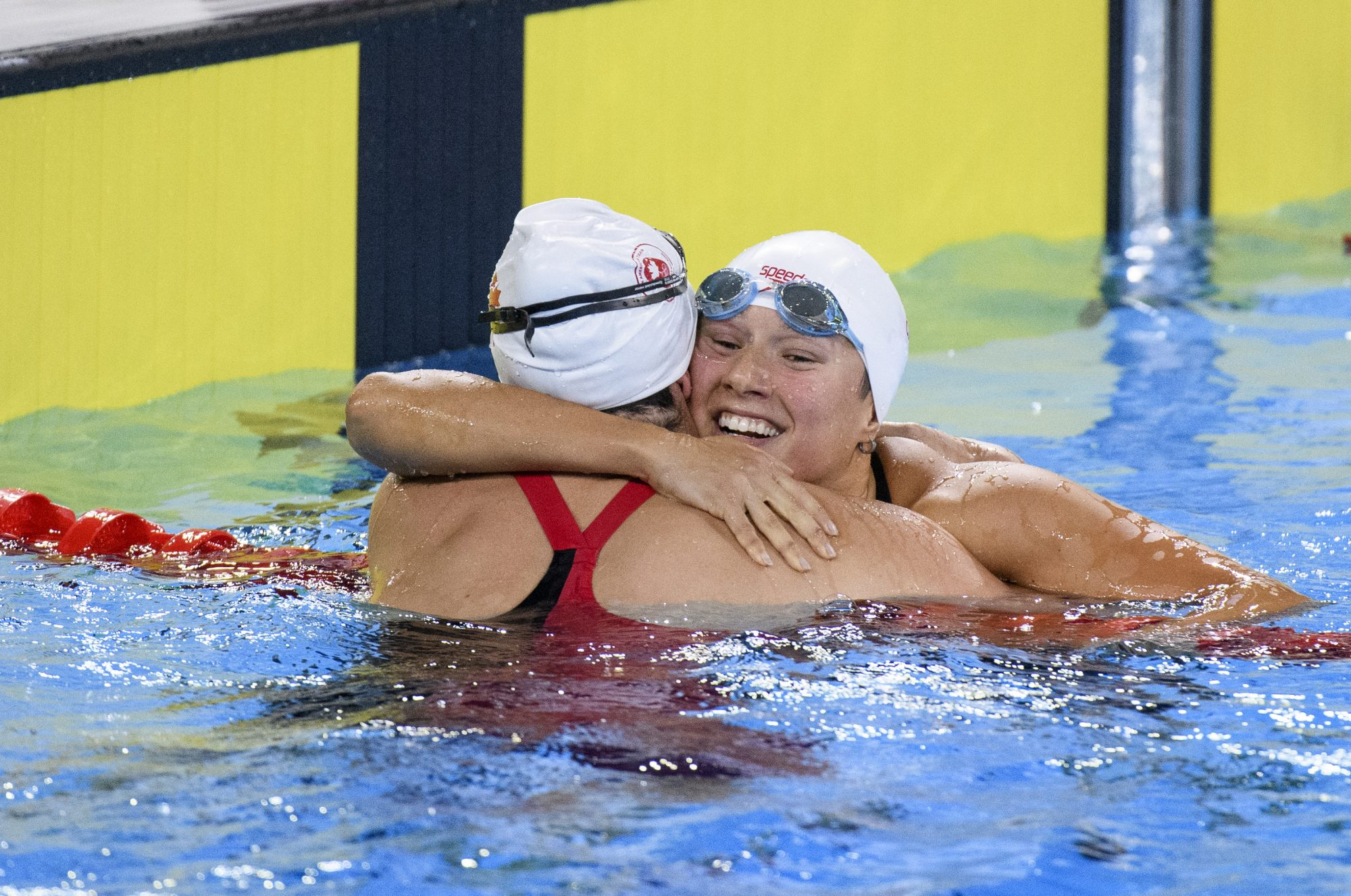 two swimmers hug in the water after a race