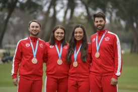 four athletes pose with their medals