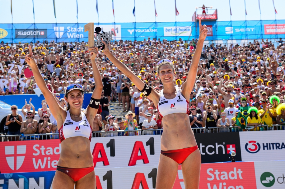Melissa Humana-Paredes and Sarah Pavan hold up their first place trophies at the Vienna stop of the FIVB Beach Volleyball World Tour.