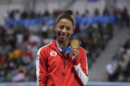 jenn abel holds up her gold medal and smiles