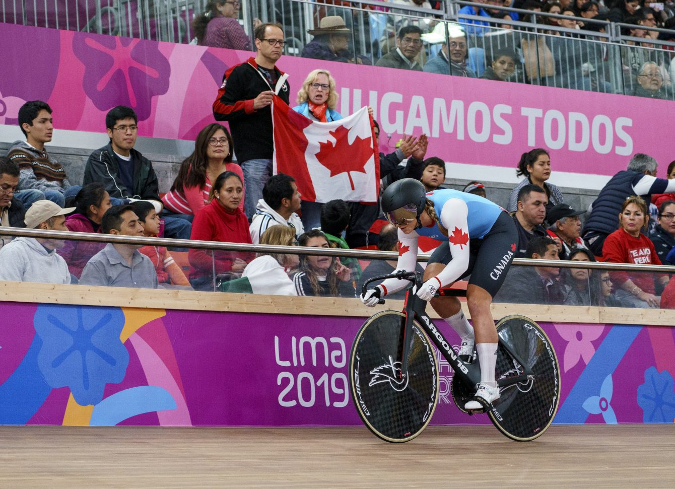 Kelsey Mitchell's parents, cheer her on holding a Canadian flag during women sprint