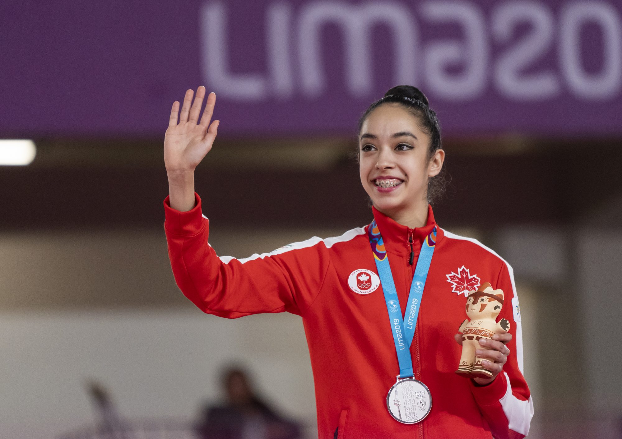 athlete waves while wearing her medal