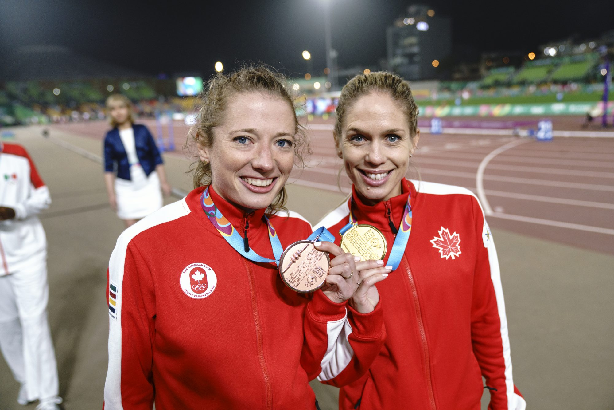 two athletes hold up their medals