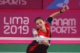 woman reaches for the badminton birdie