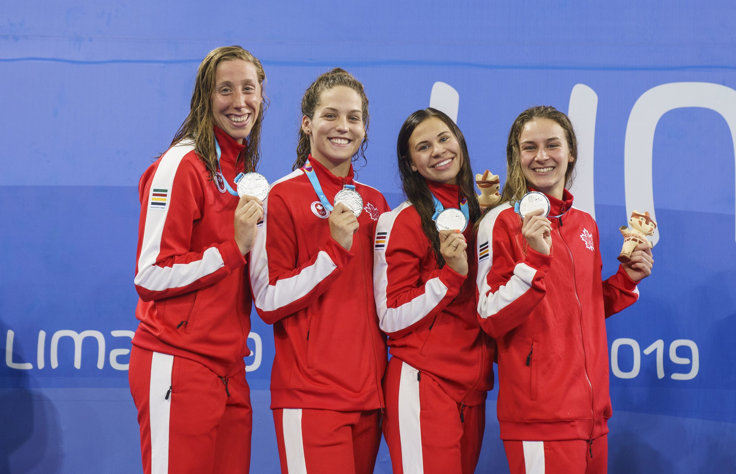 four swimmers stand on the podium holding silver medals