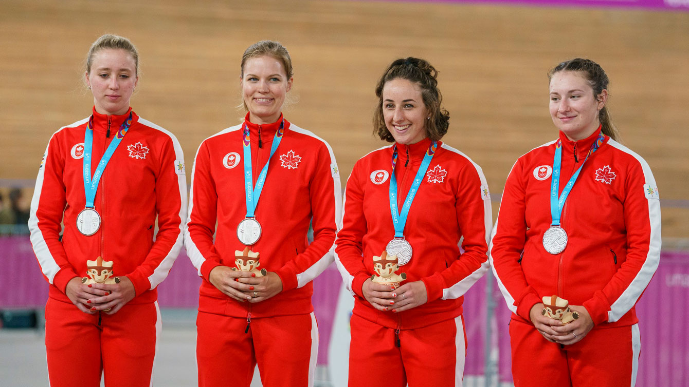 women's team stand on the podium wearing gold medals