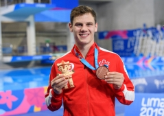athlete holds up his medal
