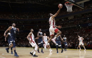 Canada's Phil Scrubb, center, scores against the USA during their exhibition basketball game in Sydney, Australia.