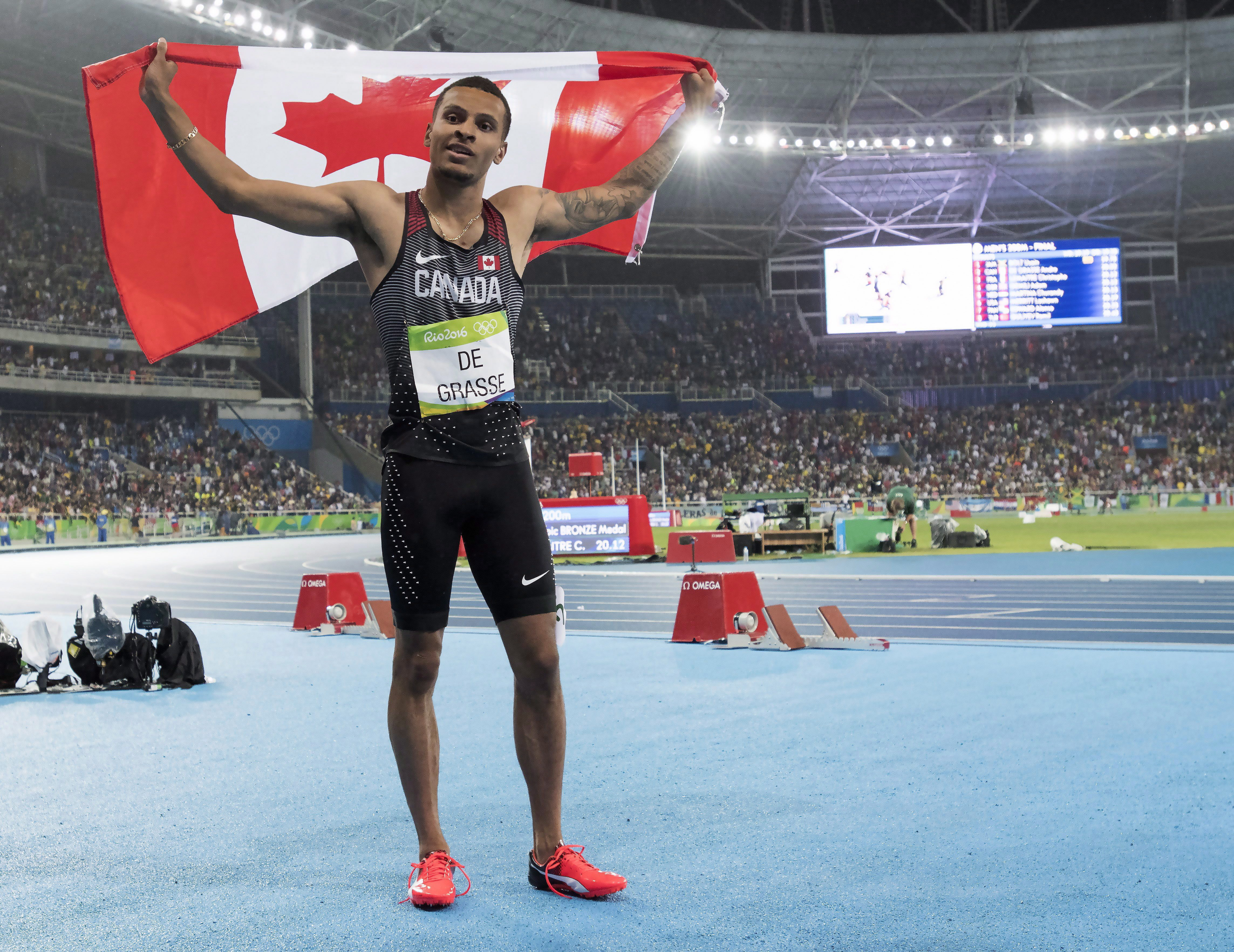 Andre De Grasse holds the Canadian flag over his head celebrating his Silver medal win.