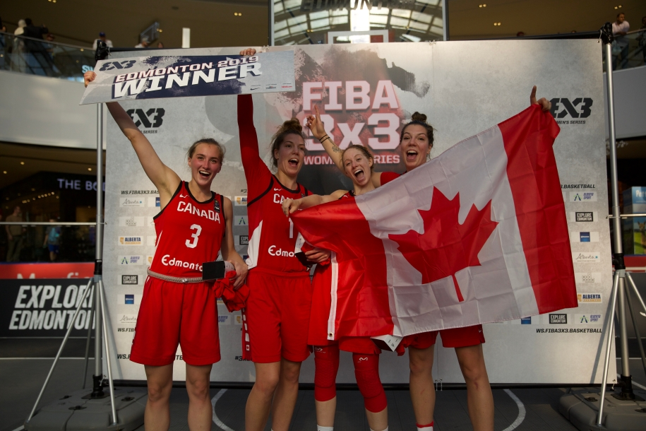 Canada's 3x3 team celebrates their victory with Paige (far left) and Michelle holding a '3x3 Edmonton 2019 Winner' sign, and Catherine and Katherine (far right) holding the Canadian flag.