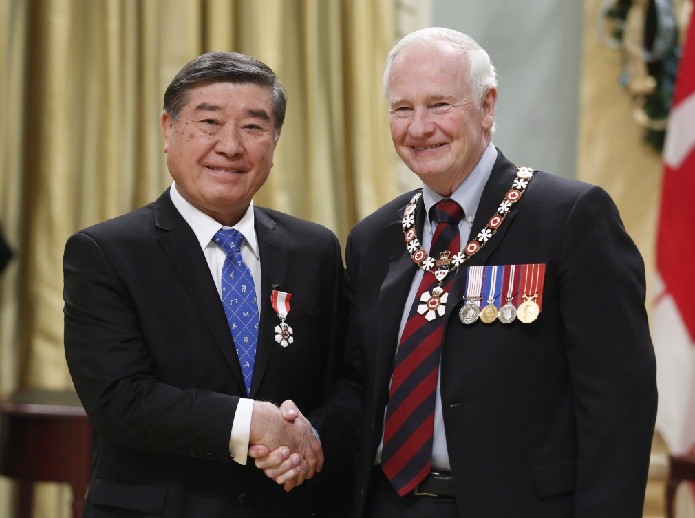 Hiroshi Nakamura (left) shakes hands with Governor General David Johnston during the Order of Canada ceremony.