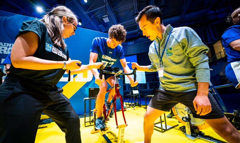 An athlete (centre) rides the sprint bike at the speed station with Patrick Chan (right) cheering him on and a staff (left) keeping track of time.