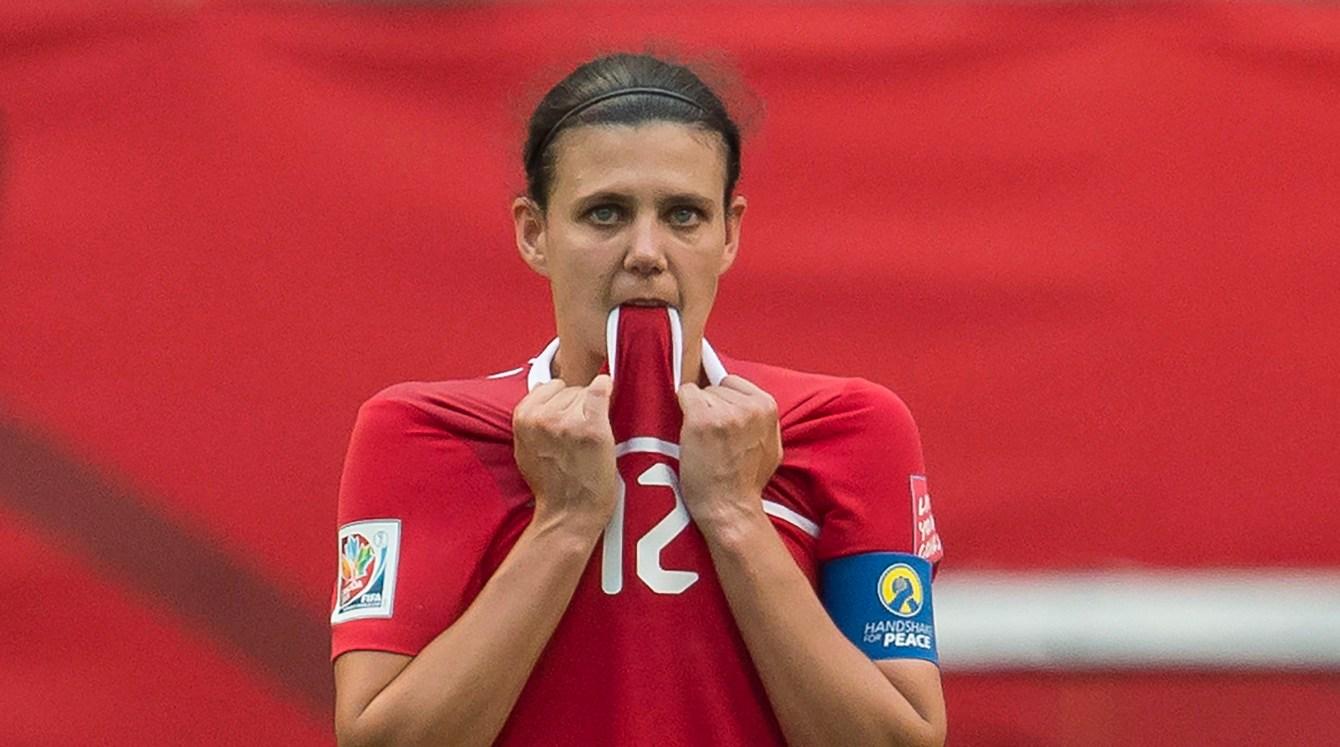 Christine Sinclair biting her jersey