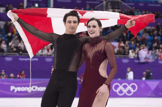 Ice dance gold medallists Canada's Tessa Virtue and Scott Moir skate with the Canadian flag