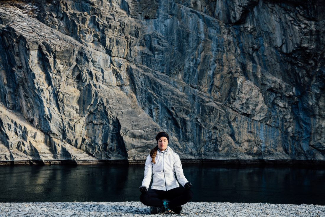 Stephanie Labbé sits cross-legged with her eyes closed in front of a lake and mountains.