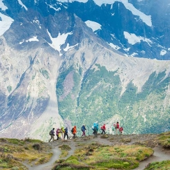 hikers walk along the base of a mountain.