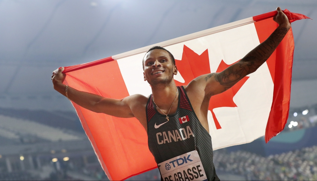 Andre De Grasse holds the Canadian flag up behind him.