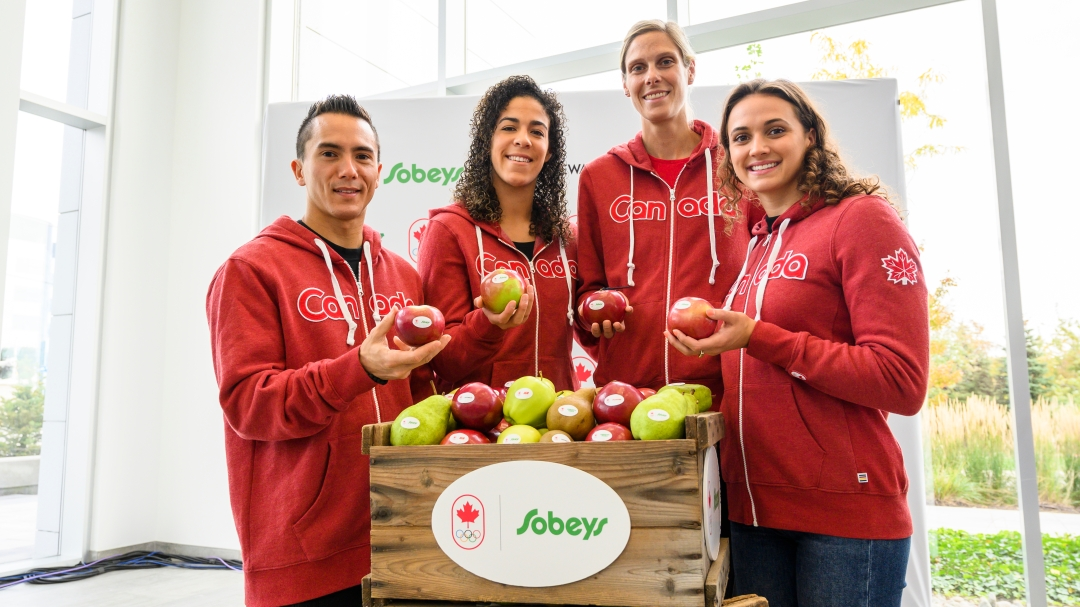 (left to right) Sean McColl, Kia Nurse, Sarah Pavan and Kylie Masse each hold an apple and stand behind a carton of apples with a Team Canada and Sobeys logo lock.