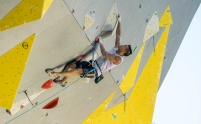 Sean McColl climbs up a wall.