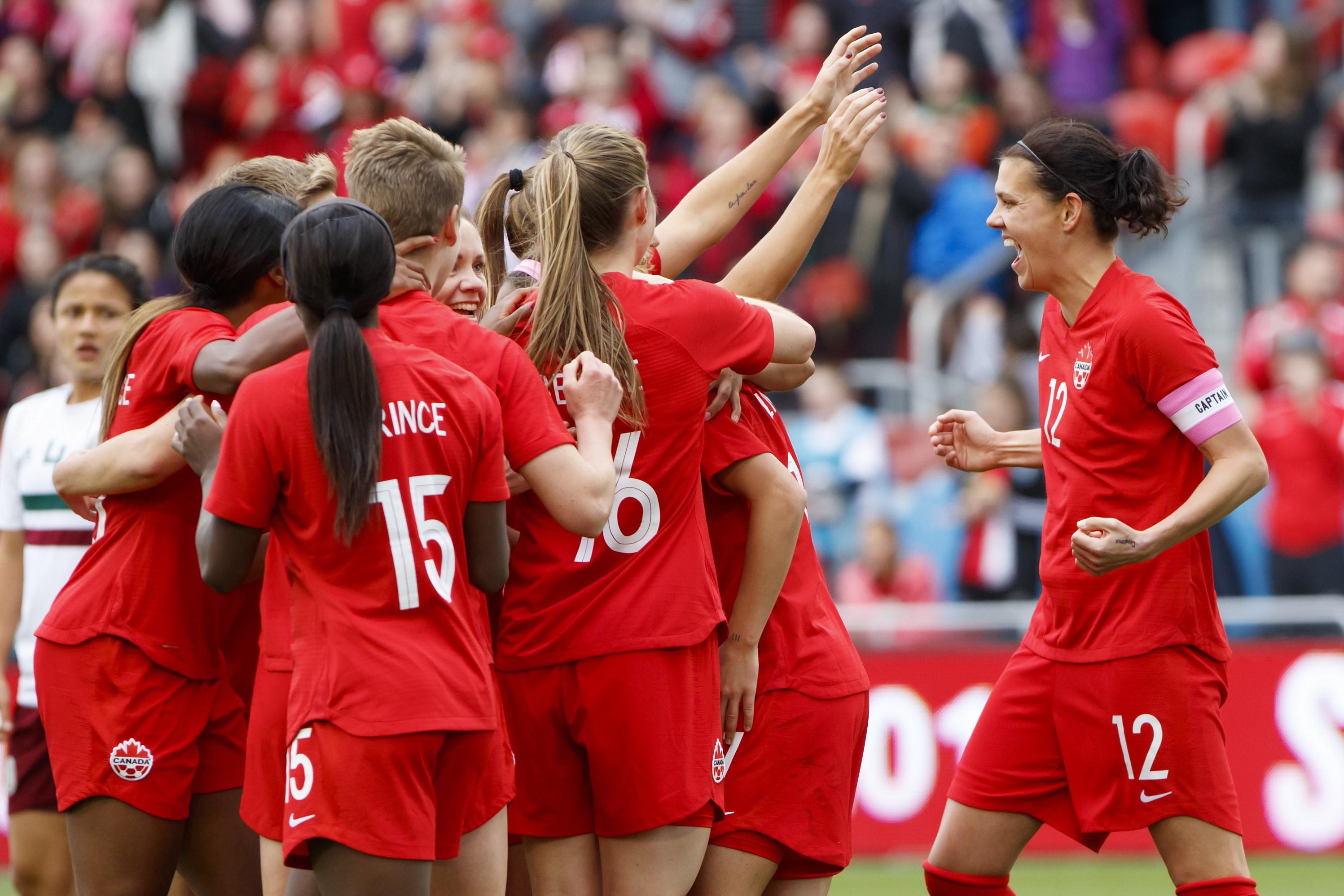 Team Canada celebrates after scoring a goal.