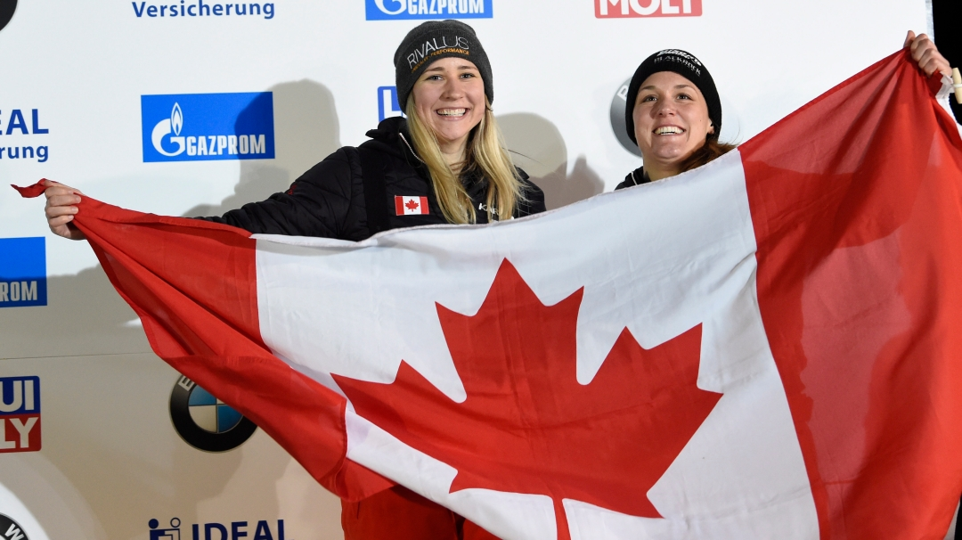 Bronze medalists Canada's Christine de Bruin, right, and Kristen Bujnowski celebrate during medal ceremony for the two-woman bobsled competition at the Bobsleigh and Skeleton World Championships in Altenberg, Germany, Saturday, Feb. 22, 2020. (AP Photo/Jens Meyer)