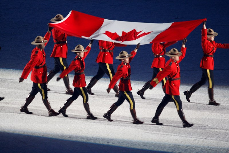 The Royal Canadian Mounted Police raise the flag high carrying it into the opening ceremonies of the Vancouver 2010 Olympics.