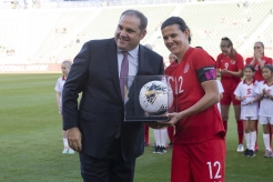 Christine Sinclair is given her record-breaking game ball by Victor Montagliani