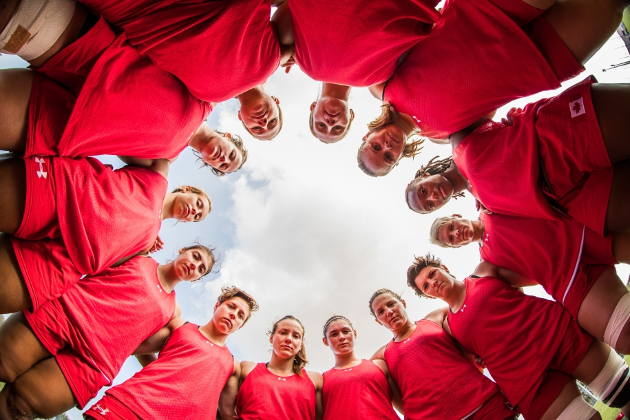 A shot from the ground up of the women's rugby team looks down at the ground while standing in a circle.