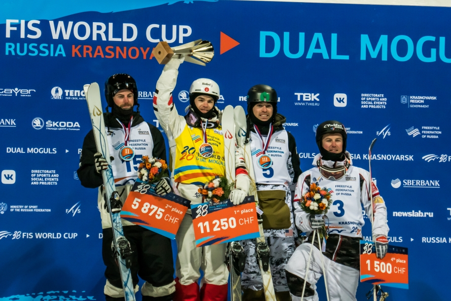 Mikael Kingsbury stands on the top step of the podium after winning gold in men's dual moguls
