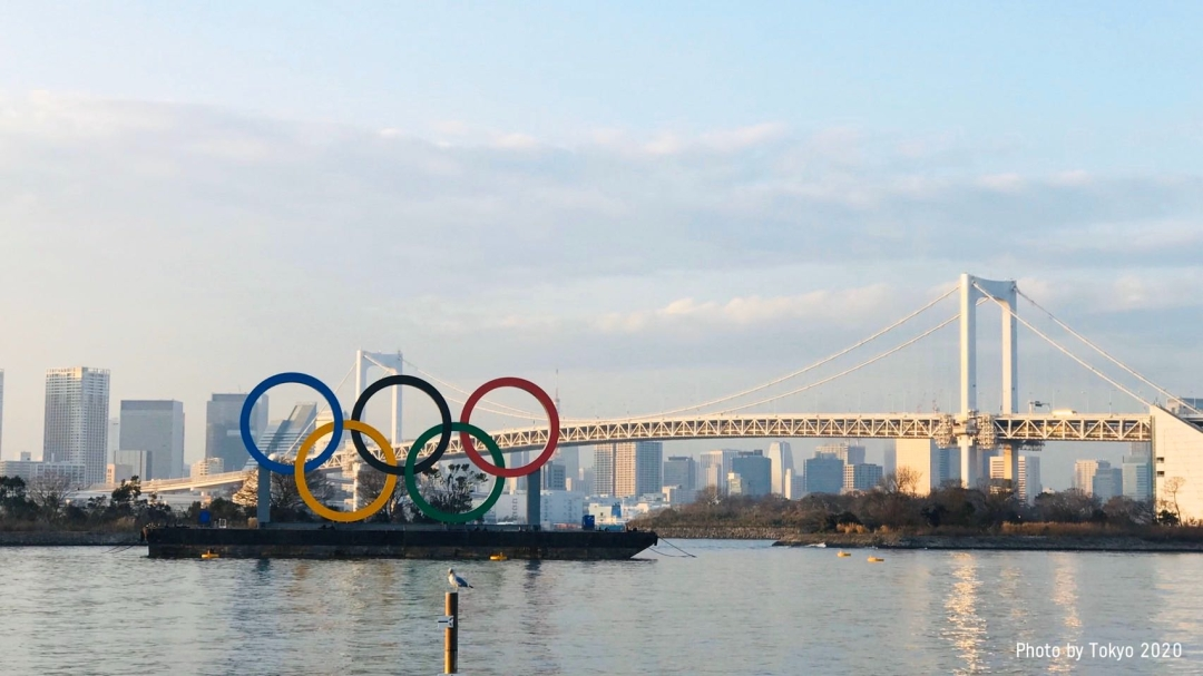 Olympic rings in front of a Tokyo bridge
