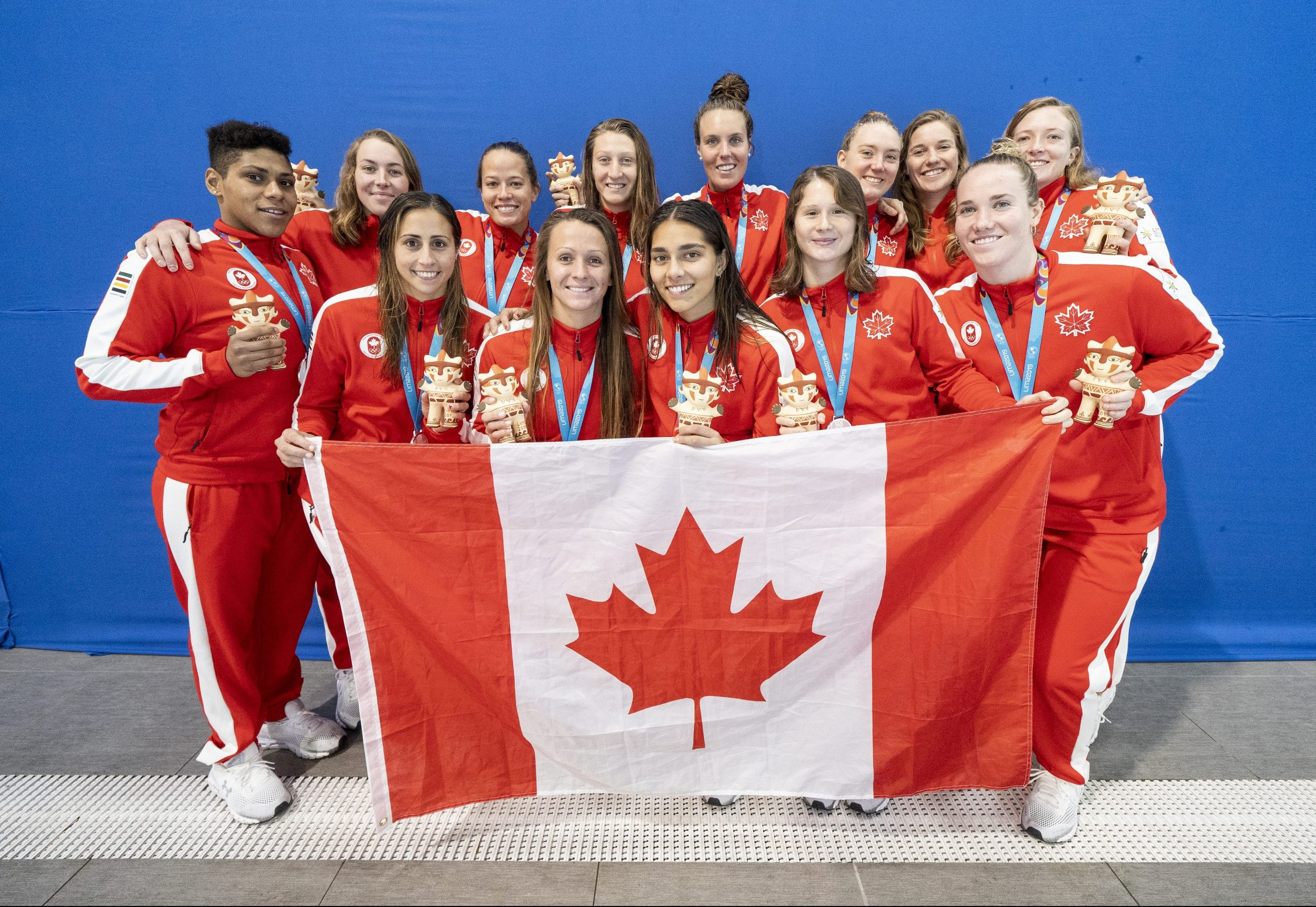 Canada's women's water polo team posed with the Canadian flag