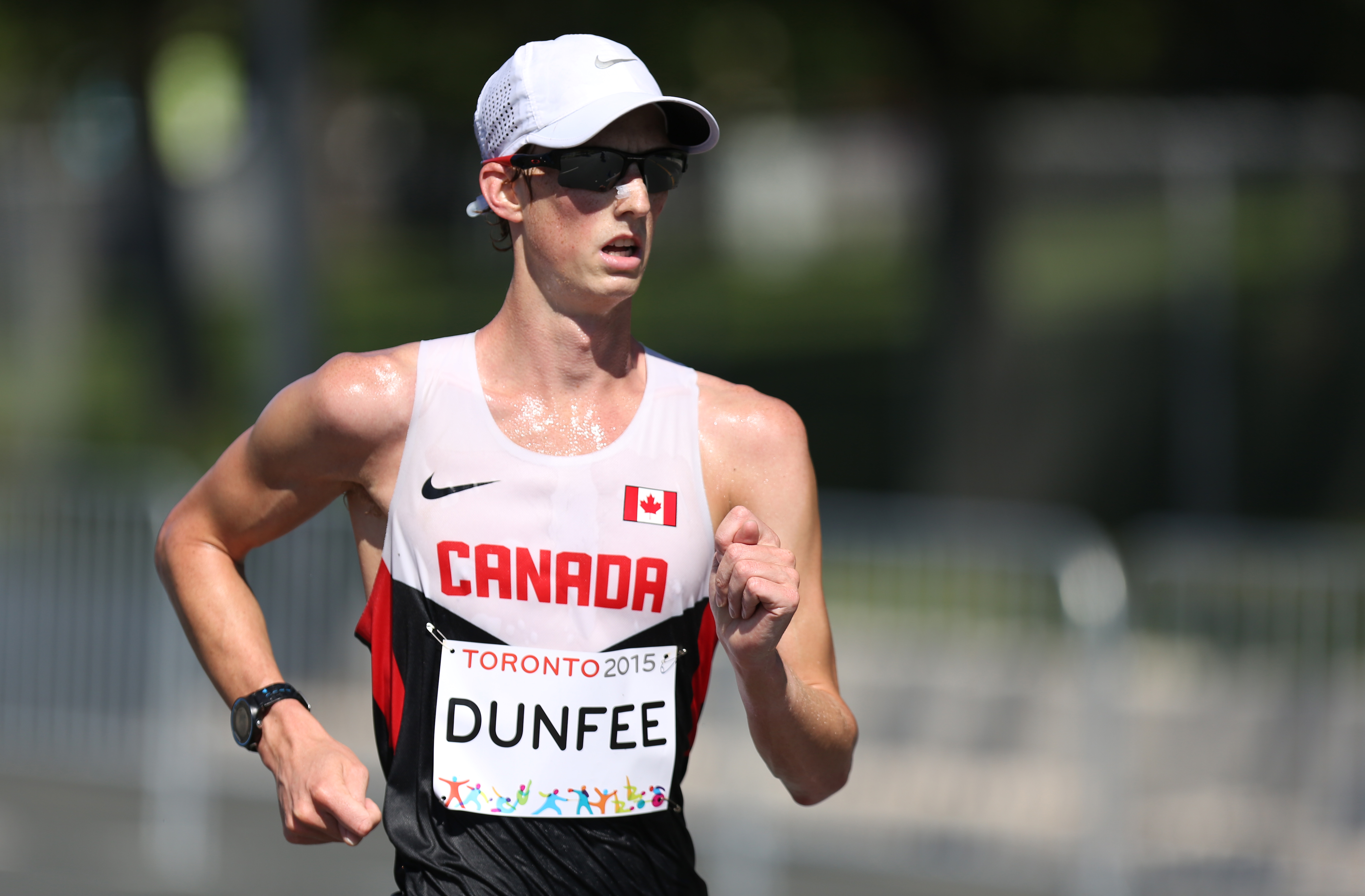 Dunfee in a racewalk with sunglasses and hat on