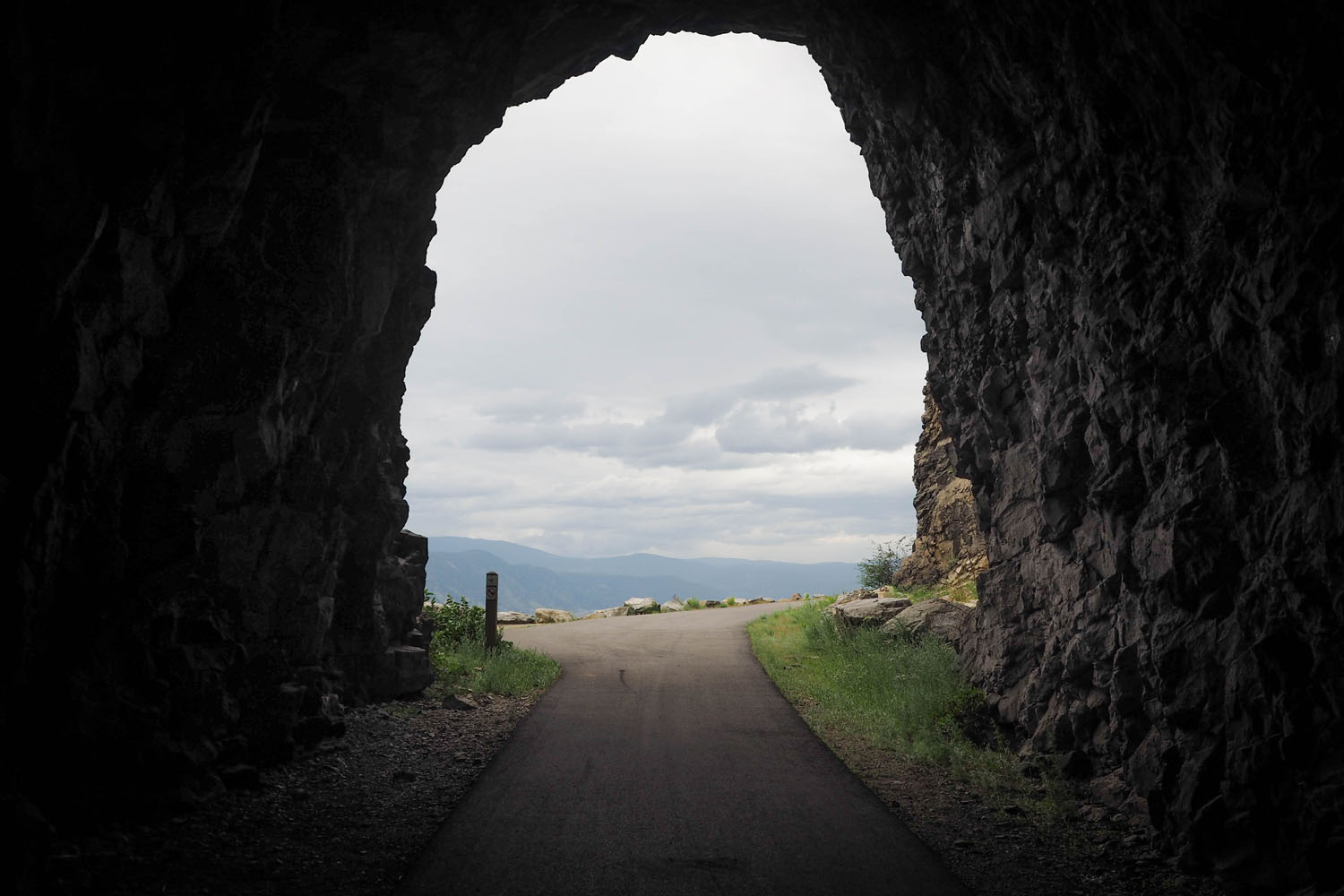 Looking through tunnel on bike trail. Looking out to hills and horizon in BC