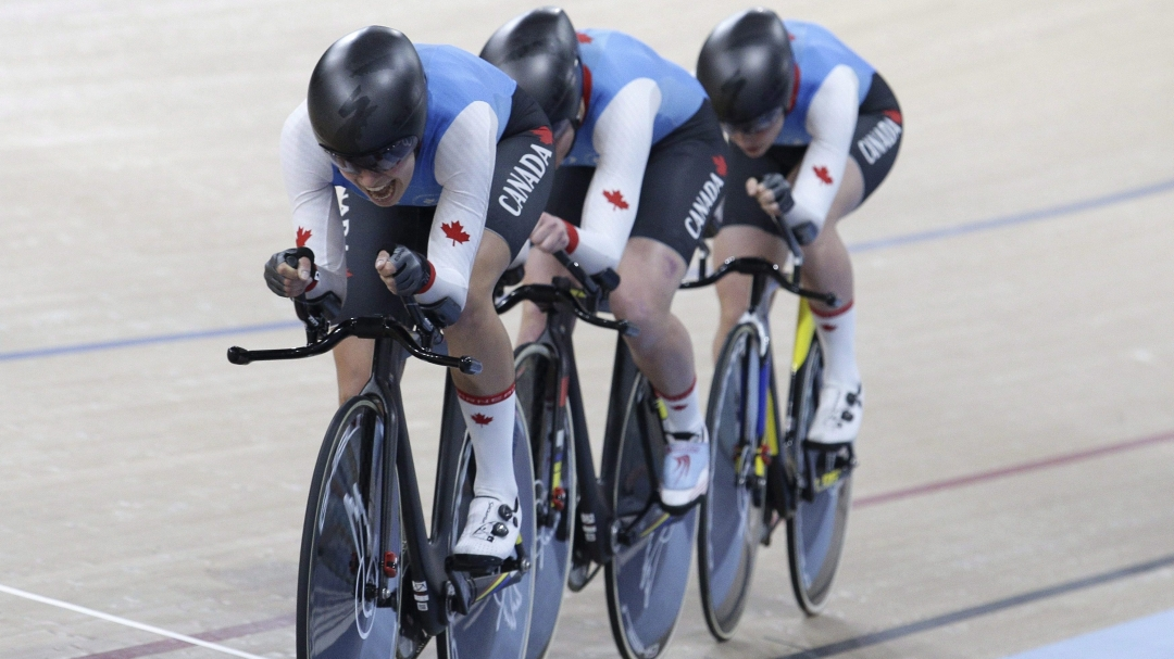 Three cyclists race team pursuit in a velodrome