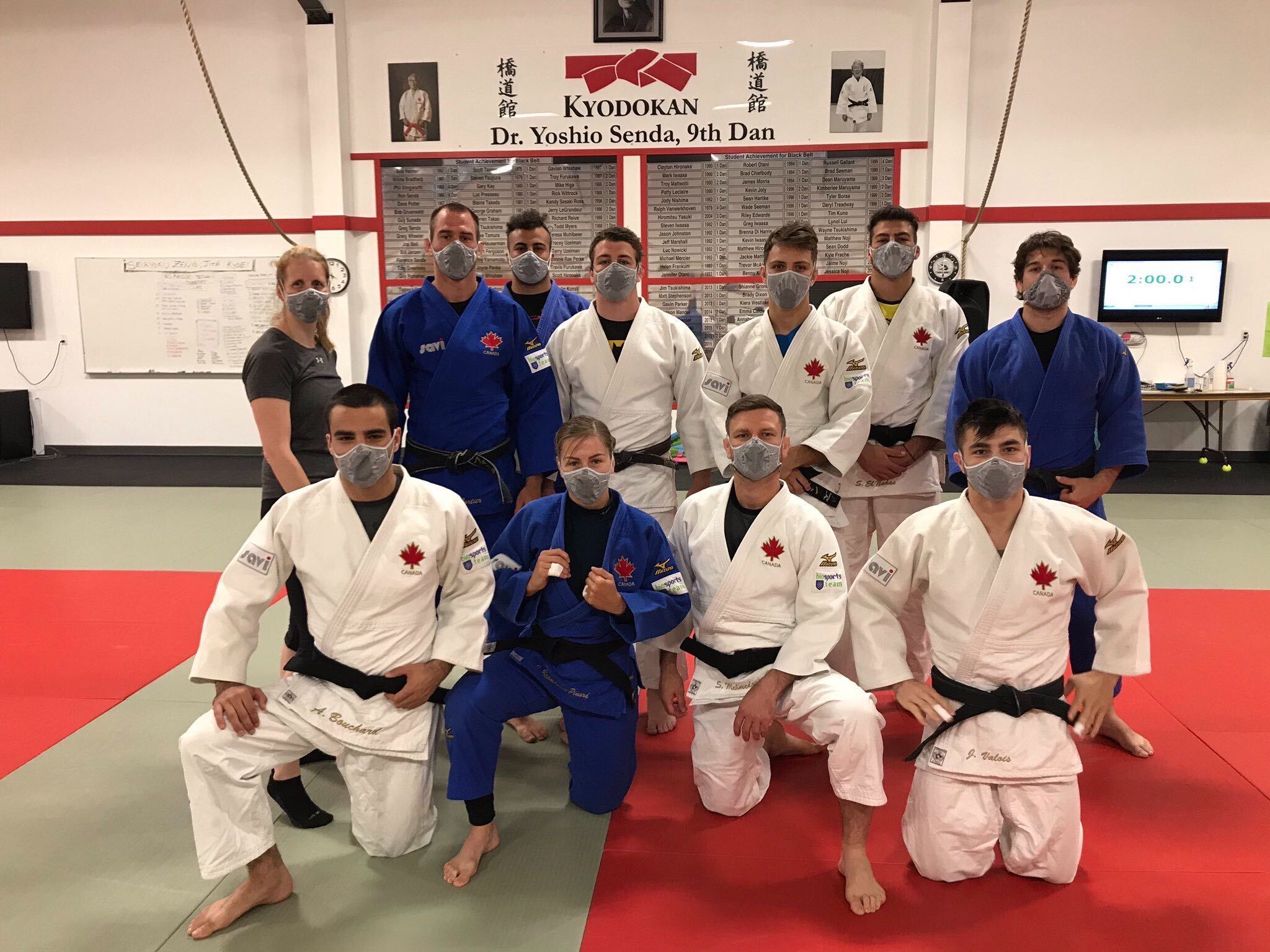 Judo national team members pose wearing masks in the dojo