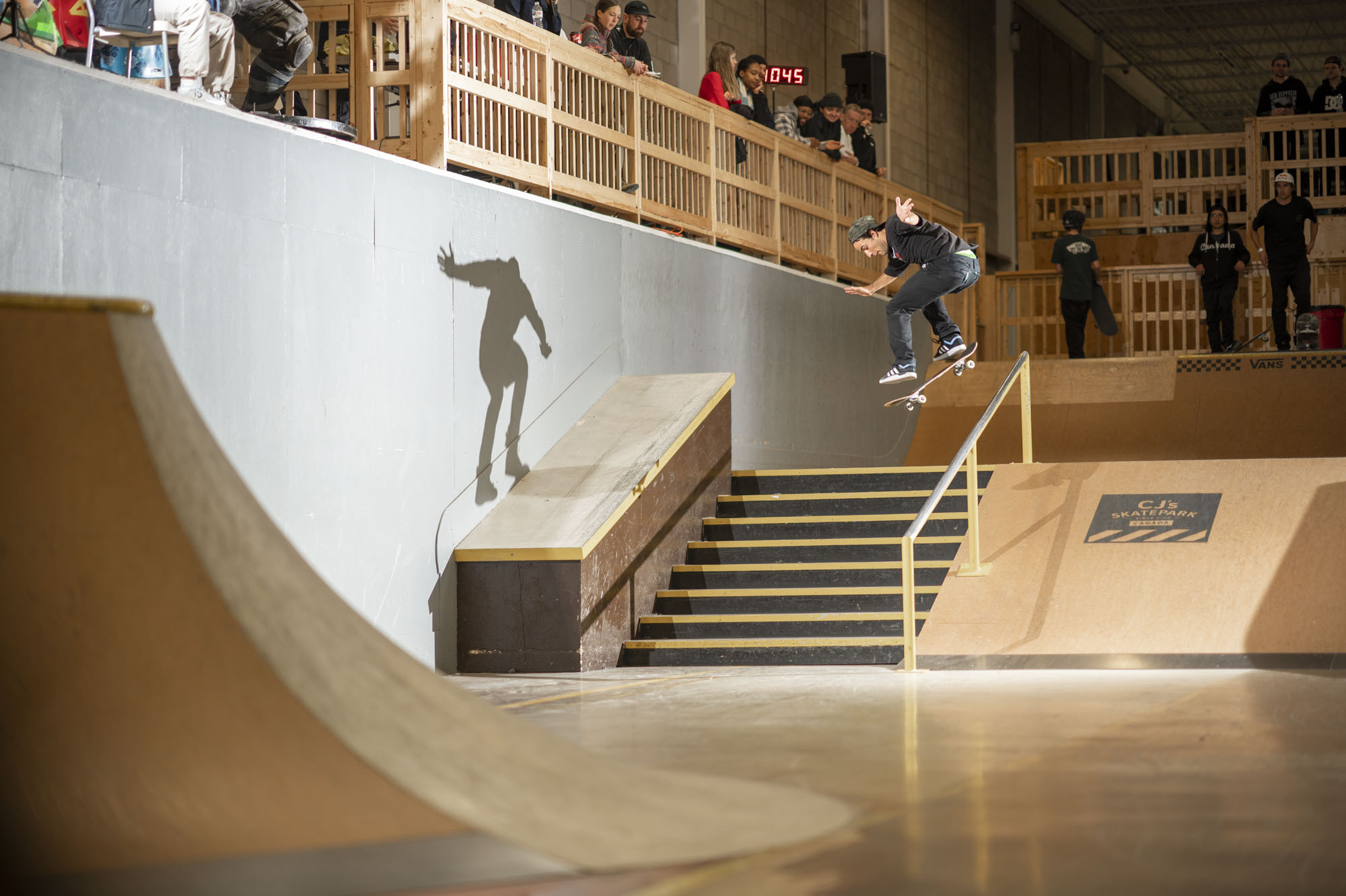 People watching Papa skate down stairs while he jumps and is airborne