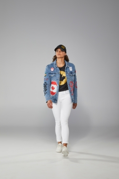Masse walking towards camera with jean jacket, white jeans, black and gold t-shirt and baseball cap