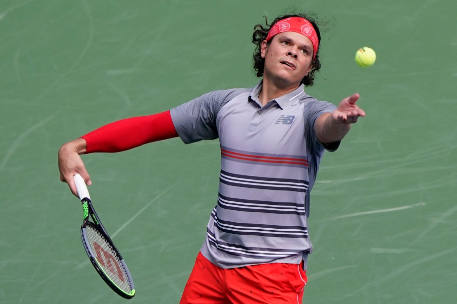 Milos throws the ball in the air to serve it.