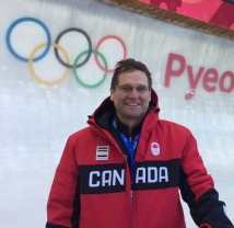 Dr. Mike smiling and standing in front of the bobsleigh track at PyeongChang 2018. He is wearing a red Team Canada winter jacket.