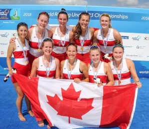 Group of Canadian rowers holding a Canadian flag