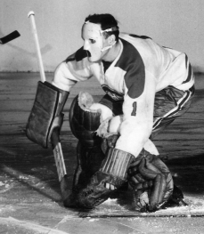 Jacques Plante squatting down in front of the goalie net in 1959 wearing his mask during a game against the Toronto Maple Leafs at Madison Square Garden.