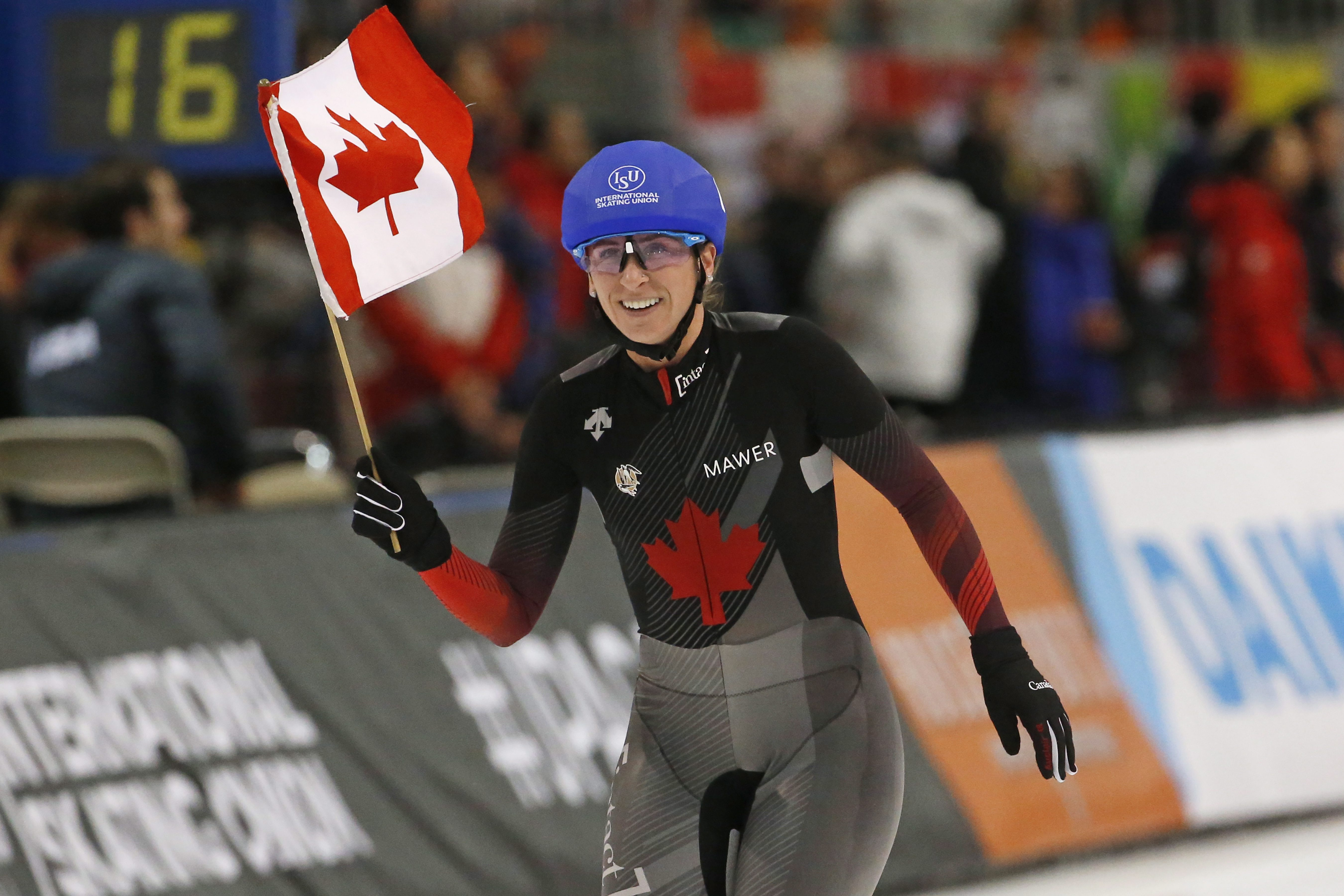 Speed skater takes victory lap waving Canadian flag