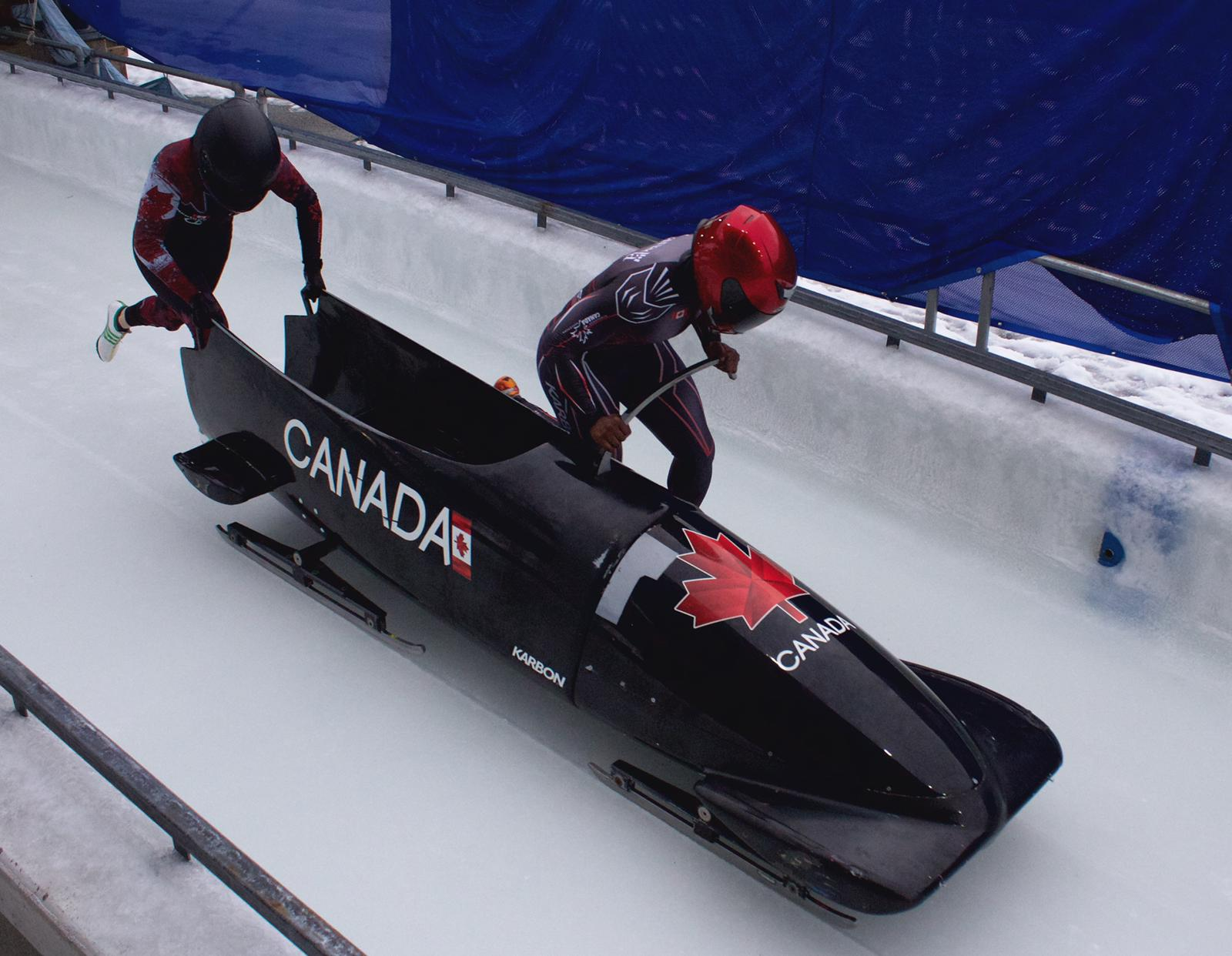 Two bobsledders push a sled at the start of a run