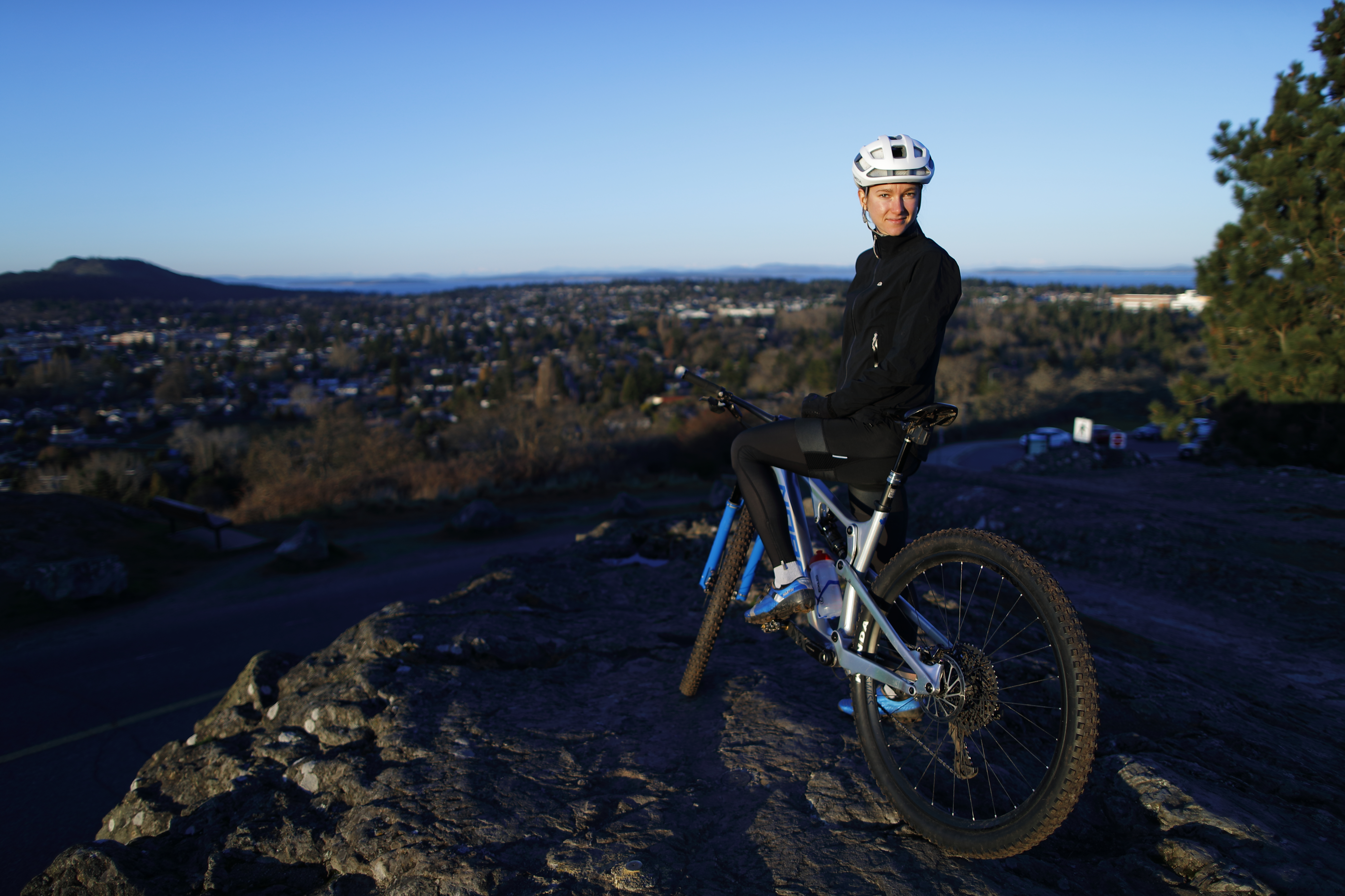 Haley Smith on her mountain bike looking over the city from a hill