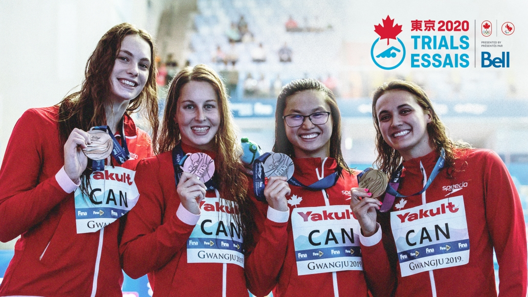 Four swimmers pose for the camera with medals