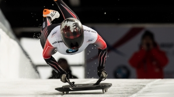Skeleton athlete dives onto sled at start of a race